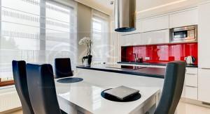 Biała kuchnia z wyspą stanowi część otwartej strefy dziennej, całość przełamuje czerwonewykończenie ściany nad blatem roboczym.