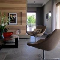 Strefa dzienna w domu jednorodzinnym. Kamienna, szara podłoga stanowi tło dla ściany fornirowanej jesionem. Kamień zastosowano również na ścianie.  Wielkie tafle szkła wpuszczają światło do wnętrza. Naturalne materiały i kolory. Miękkość i szorstkość użytych materiałów.