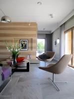 Strefa dzienna w domu jednorodzinnym. Strefa relaksu, wypoczynku. Tu można wygrzewać się przy kominku, oglądać TV, być. Kamienna, szara podłoga stanowi tło dla ściany fornirowanej jesionem. Kamień zastosowano również na ścianie.  Wielkie tafle szkła wpuszczają światło do wnętrza. Naturalne materiały i kolory. Miękkość i szorstkość użytych materiałów.