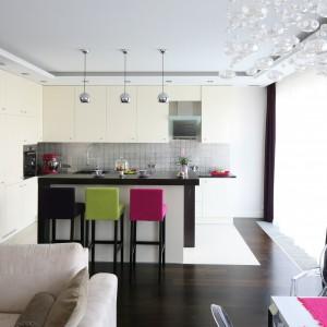 Salon płynnie łączy się z jadalnią i kuchnią, tworząc jedną, wspólną przestrzeń. Subtelną granicę między strefą roboczą a wypoczynkową wyznacza jedynie wysoki bar z kolorowymi hokerami. To świetne miejsce na poranną filiżankę kawy. Projekt: Agnieszka Żyła. Fot. Bartosz Jarosz.