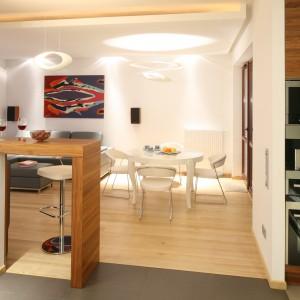 Wysoki bar, wykończony ciemnym drewnem, stanowi granicę między kuchni a salonem, dyskretnie przysłaniając przed gośćmi strefę roboczą. Projekt: Paweł Pałkus, Kuba Kasprzak. Fot. Bartosz Jarosz.