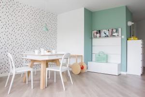 Białe, proste meble doskonale komponują się z jasną, drewnianą podłogą i drzwiami, a szaroturkusowa ściana rozwesela to niewielkie wnętrze.