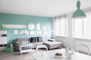 Dużą rolę odgrywa tutaj światło. Okna zostały ozdobione żaluzjami, którymi można manipulować swobodnie dozując i zmieniając oświetlenie naturalne w ciągu dnia. Kompozycja luster na ścianie również rozświetla i powiększa wnętrze, a designerskie lampki dopełniają efektu.