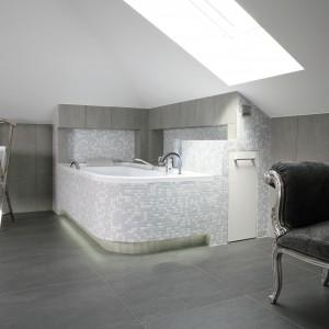 Wystrój łazienki tworzą ciemne grafitowe płytki na podłodze, nieco jaśniejsze na ścianach oraz mozaika o szaro-błękitnej barwie na obudowie wanny. W obudowie wanny znajdują się również podświetlone półki. Projekt: Dominika Grabowska. Fot. Bartosz Jarosz.