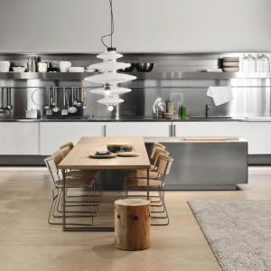 Kuchnia z kolekcji Spatia idealna do otwartego wnętrza. Biel połączona ze stalą nadaje je nowoczesny, minimalistyczny charakter. Całość ociepla drewniany stół w komplecie z krzesłami. Wycena indywidualna, Arclinea.