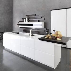 Eleganckie, proste i nowoczesne meble kuchenne z kolekcji Solo. Wysoka zabudowa zapewnia miejsce na przechowywanie, natomiast wyspa stanowi funkcjonalne centrum gotowania. Białe fronty w połysku idealnie łączą się z ciemnym drewnem dębu. Wycena indywidualna, Rational.