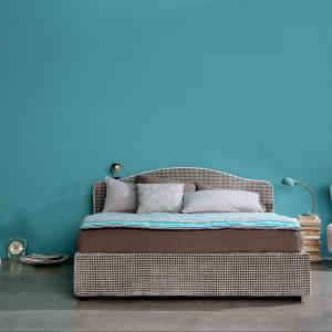 Tapicerowane łóżko w odcieniach ciepłych barw ziemi idealnie eksponuje się na tle turkusowej ściany. Fot. Letti.