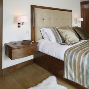Podwieszane stoliki nocne oraz kinkiety nadają masywnej bryle łóżka nieco zwiewności. Fot. Bartosz Jarosz