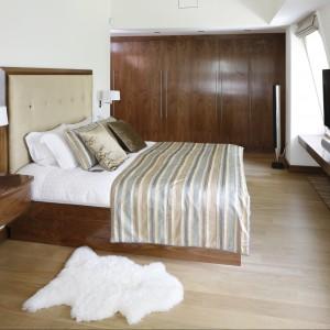 W przestronnej sypialni dominuje drewno. Jej aranżacja łączy w sobie elementy tradycyjne z nowoczesnymi. Fot. Bartosz Jarosz