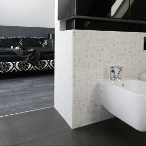 Przestronny salon kąpielowy połączona z sypialnią właścicieli zachowując przy tym rygor czarno-białej stylistyki. Projekt Paweł Kubacki. Fot. Bartosz Jarosz.