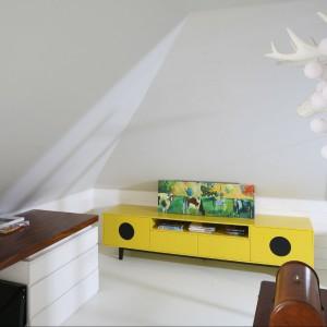 W minimalistycznym wnętrzu pojawiają się akcenty rozbijające jednolity charakter: żółta szafka, odrestaurowana maszyna do szycia oraz wiszący nad nią gipsowy odlew – trofeum z jelenia z lampą w formie wełnianych baniek. Fot. Bartosz Jarosz.