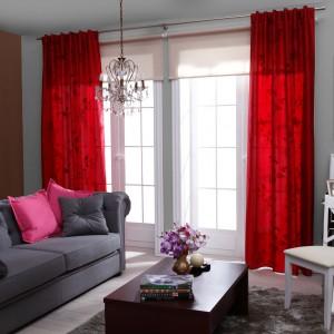 Pokój w ciekawym eklektycznym stylu - elementy glamour, takie jak piękny dekoracyjny  żyrandol, zestawiono z nowoczesną dekoracją okna, w której największą uwagę zwraca intensywnie czerwona zasłona Pianta Mardom. Sprzedaż: www.nexterio.pl.