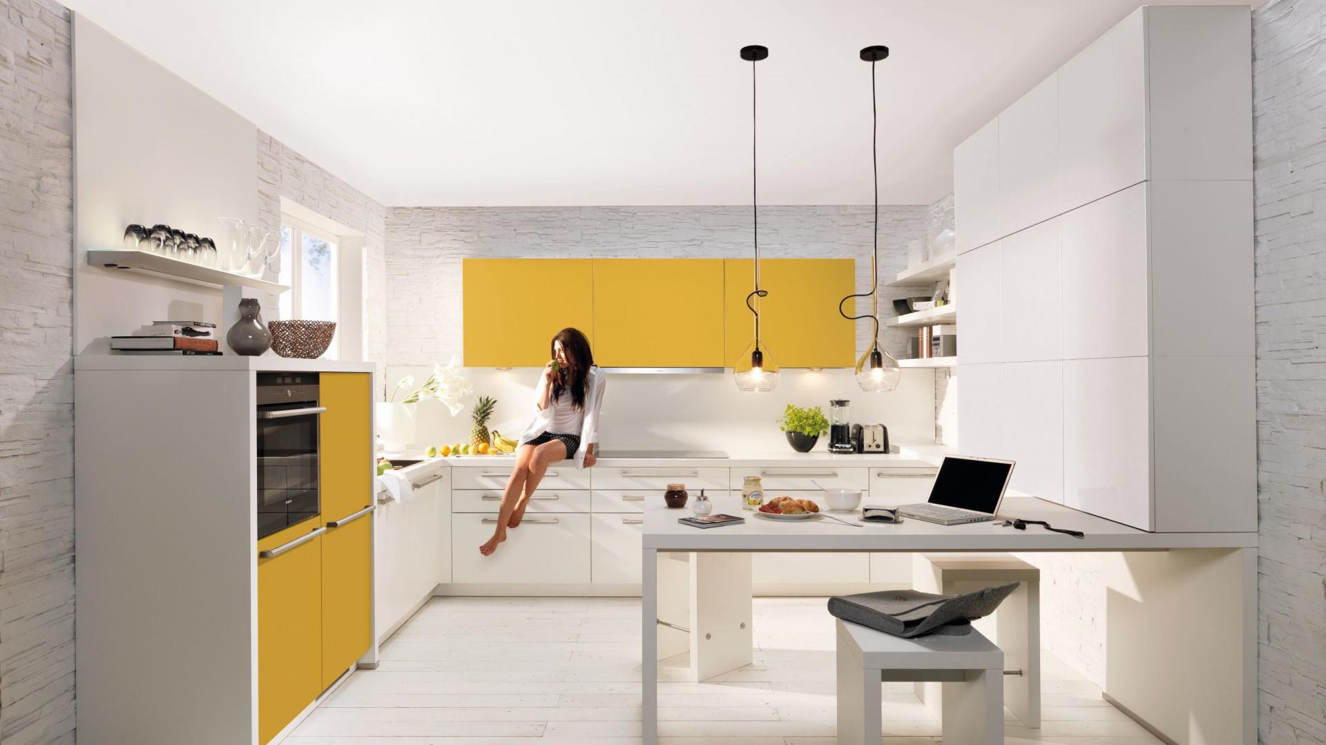 Meble kuchenne z kolekcji Soft Lack. Biel zastosowaną we wnętrzu w zdecydowanej przewadze ocieplają fronty w ciepłym, żółtym kolorze. Całość prezentuje się lekko i stylowo. Wycena indywidualna, Nolte Küchen.