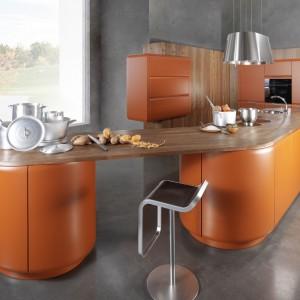 Meble kuchenne z kolekcji Onda. Pomarańczowy kolor frontów jest idealnym partnerem dla ciemnego drewna. Kuchnia jest nowoczesna, ale ciepła i domowa. Wycena indywidualna, Rational.