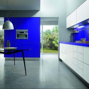 Meble kuchenne z kolekcji Silverbox. Dolne i górna szafki w białym kolorze ożywia mocny odcień niebieskiego,  który pojawia się na ścianie między nimi oraz na samym blacie. Zastosowano go również na frontach wysokiej zabudowy. Wycena indywidualna, Ernestomeda.