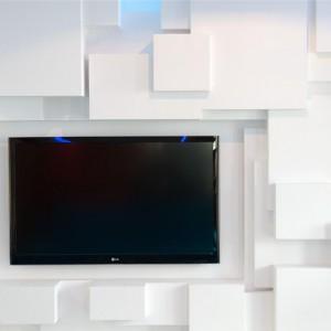 Ciekawy pomysł na ścianę telewizyjną - białe trójwymiarowe panele ścienne. Fot. Hola Design.