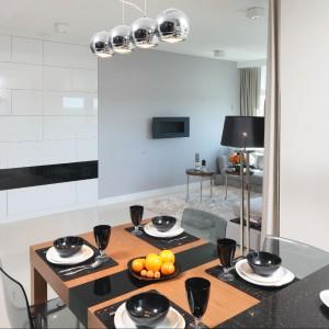 Wspólna przestrzeń kuchni i salonu została umownie podzielona. Zaraz po wejściu do mieszkania na pierwszym planie ukazuje się elegancka kuchnia. Fot. Bartosz Jarosz.