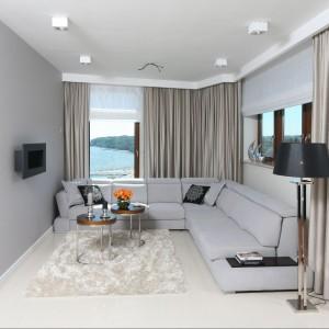 W salonie, z niezwykłym widokiem na morze, zamiast telewizora zamontowano kominek. Piękną dekorację stanowią lśniące, lejące się zasłony oraz puszysty dywan. Komfortowy narożnik wypełnia niemal całą przestrzeń pomieszczenia. Fot. Bartosz Jarosz.