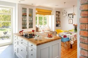 Kuchnia z wyspą i jadalnią. Lekka i kolorowa, przytulna, ale funkcjonalna. Część jadalnianą od kuchennej rozdziela wyspa z dużą ilością szuflad i schowków. Aranżacja stołu oraz różnokolorowe krzesła dodają energii, a biała kuchnia wpisuje się w panujące trendy.