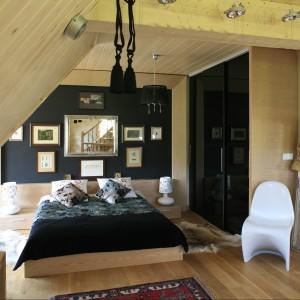 Obudowana jasnym, ciepłym drewnem sypialnia to wnętrze ulokowane bezpośrednio na piętrze, co zapewniło mu otwartą, dużą przestrzeń. Przytulna, naturalna baza posłużyła jako tło dla wyposażenia w ciemnym kolorze. Projekt Agnieszka Burzykowska-Walkosz Fot. Bartosz Jarosz