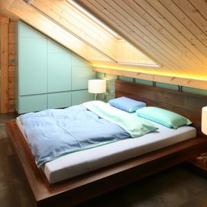 Ulokowana na poddaszu sypialnia dzięki jasnej drewnianej boazerii zyskała trochę przytulności i ciepła. Projekt Tomasz Motylewski, Marek Bernatowicz. Fot. Bartosz Jarosz