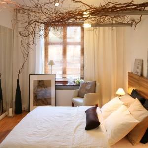 Oryginalne gałęzie wierzby mandżurskiej po sufitem podkreślają nietuzinkowy charakter utrzymanej w jasnej kolorystyce sypialni. Projekt Urszula Górska-Iwicka i Jakub Górski Fot. Bartosz Jarosz