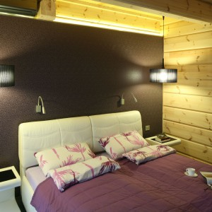 Drewniane ściany sypialni doskonale współgrają z brązową fototapetą, idealnie wpisując się w nowoczesną aranżację wnętrza. Projekt Tomasz Motylewski, Marek Bernatowicz. Fot. Bartosz Jarosz