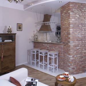 Ścianka z rdzawej, palonej cegły wyznacza granicę między kuchnią a salonem, nadając przestrzeni ciepły, domowy klimat. Od strony kuchni skrywa lodówkę, natomiast wnęki po przeciwnej stronie wykorzystano jako leżak na wino. Projekt: Aleksandra Urban. Fot. Monika Filipuk-Obałek.