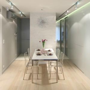 Projekt wnętrza bazuje na inspiracji stylem skandynawskim. Nowoczesny stół z blatem z kompozytu oraz transparentne krzesła doskonale komponują się z neutralnym tłem okładzin. Projekt: Monika i Adam Bronikowscy. Fot. Bartosz Jarosz.