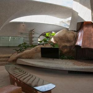 Część wypoczynkowa: warto zwrócić uwagę na kamienny kominek i wkomponowany w jego bryłę zupełnie współczesny telewizor. Fot. Organicmodernestate.com, TKK Represents.