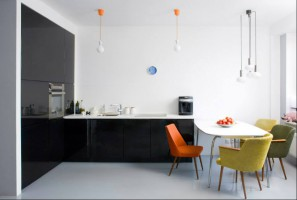 Kuchnia z jadalnią - minimalistyczna, w kontrastowych kolorach, z żywym akcentem ciepłych kolorów.
