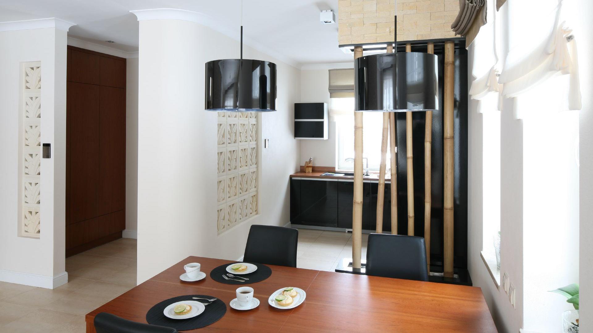 Kuchnia ulokowana jest we wnęce, a tuż o krok, przy oknie, stworzono strefę jadalnianą z własnym oświetleniem.