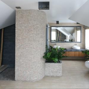 Prysznic ukryty jest za dobudowaną, półokrągłą ścianką. Całą konstrukcję obłożono łupanym marmurem, dzięki czemu stanowi bryłę ciekawie zarysowaną w przestrzeni łazienki. Parę umywalek umieszczono na solidnym, kamiennym blacie.  Fot. Bartosz Jarosz.