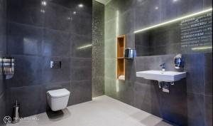 """Przestrzenią wybijającą się pośród pastelowych kolorów jest toaleta dla pacjentów. Występująca w roli """"jamy skalnej"""" zaskakuje kamiennym chłodem i elegancją. Zastosowanie ciemnej farby na suficie, dzięki znacznej wysokości pomieszczenia, nie pomniejszyło go, ale sprawiło wrażenie przytulności. W formie ocieplenia występują drewniane szafki."""