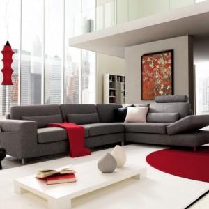 Czerwony dywan, lampy i koc wnoszą do szaro-białego wnętrza optymizm i pozytywną energię. Fot. Colombini Casa.