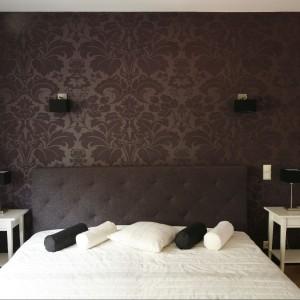 Sypialnia z dużym tapicerowanym łóżkiem i pasującą do niego tapetą w stylu glamour. Fot. Bartosz Jarosz.