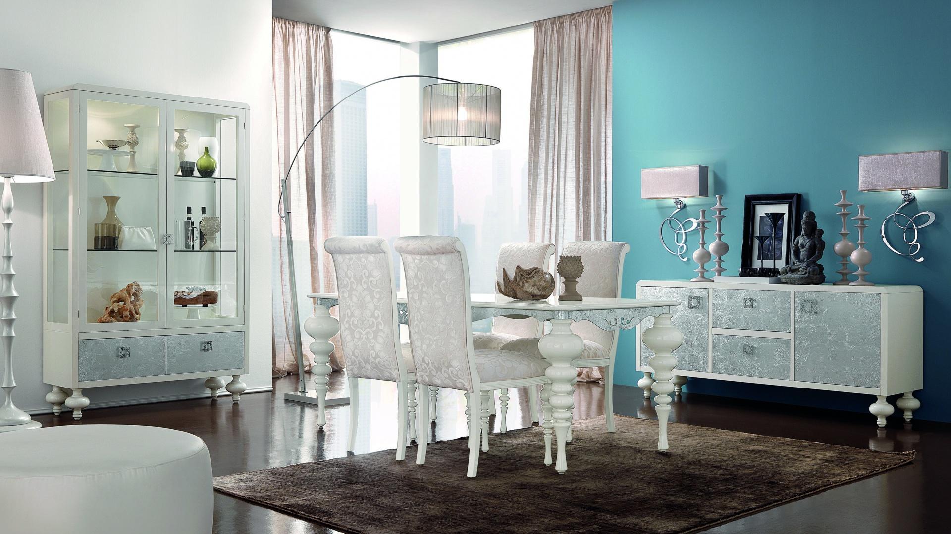 To propozycja zestawu mebli do jadalni od firmy Bova. Stół z kolekcji Victoria, szafki z kolekcji Vetrina, tapicerowane krzesła z kolekcji Lady. Białe wykończenia w satynowym połysku nadają wnętrzu elegancki, stylowy charakter.