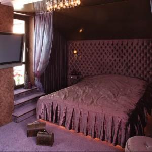 W tej sypialni fioletowe jest wszystko. Nie znaczy to jednak, że wszystko jest takie same. Ciepłe odcienie fioletu mieszają się z tymi chłodniejszymi dodając wnętrzu dynamiki. Tapicerowane łoże wydobywa luksusowy charakter tej barwy. Projekt Dorota Banasik Fot. Bartosz Jarosz
