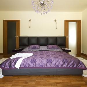 Duże, tapicerowane łoże jest głównym meblem w sypialni. Zdobi je fioletowa połyskująca narzuta z klasycznym ornamentem. Do niej dobrano kryształowy żyrandol w lawendowym odcieniu. Projekt Tomasz Tubisz Fot. Przemysław Andruk