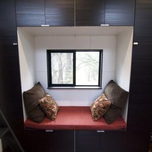 Przestrzeń do wypoczynku z oknem, przez które można oglądać krajobraz. Fot. TinyHouseBuild.