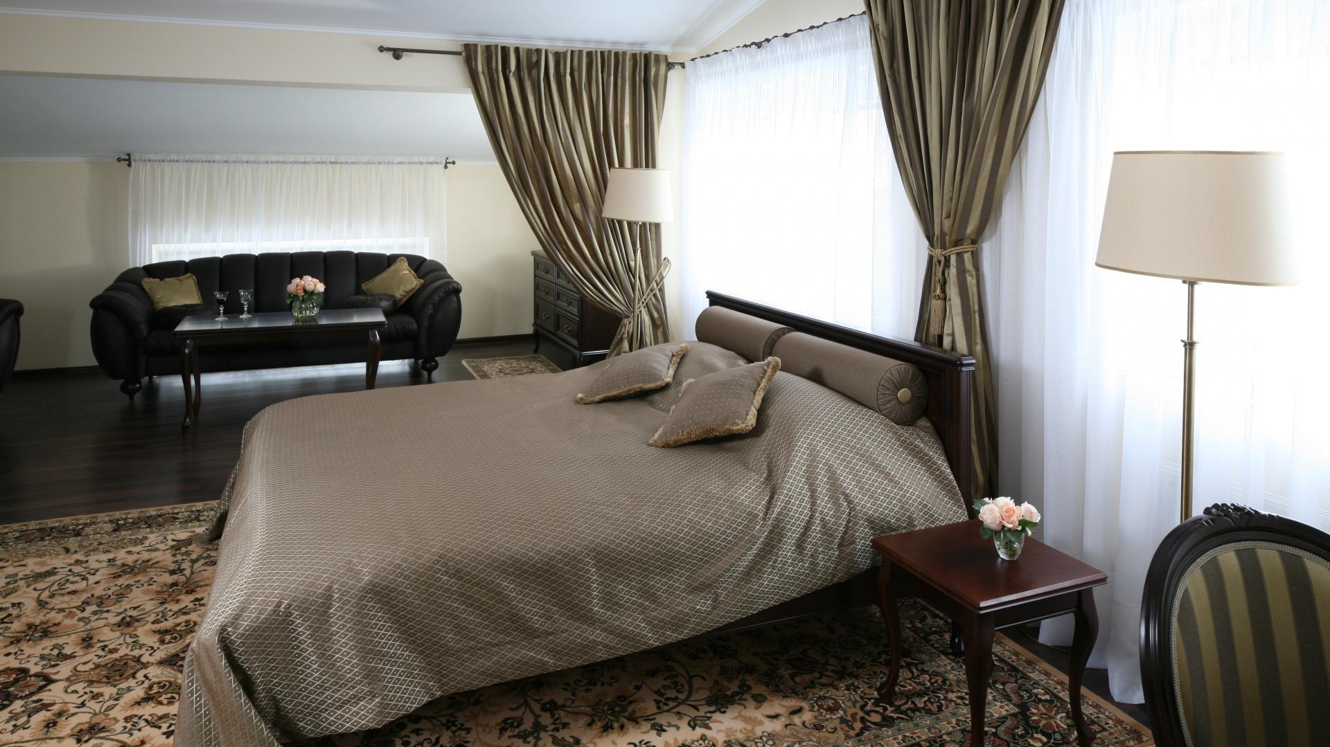 Przestronną sypialnię urządzono w stylu klasycznym. Główne miejsce zajmuje tu tradycyjne, drewniane łoże. Projekt Małgorzata Goś. Fot. Bartosz Jarosz