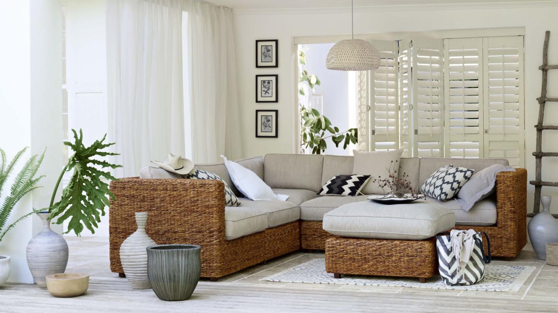 Elegancka sofa narożna i pufa z naturalnego rattanu wnoszą do białego wnętrza znamiona stylu safari. Fot. Marks & Spencer.