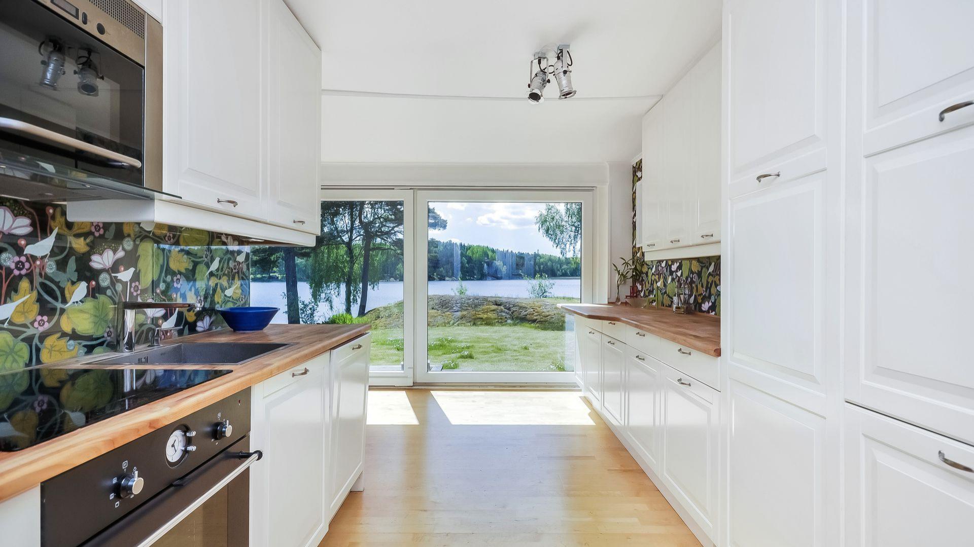 Prosta naturalna kuchnia z białymi, drewnianymi meblami w tradycyjnym stylu. Fot. Svenskfast.se.