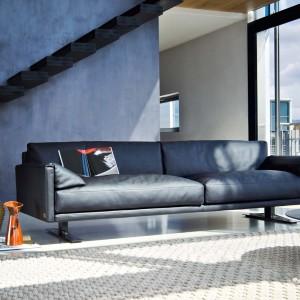 Elegancki wygląd salonu podkreśla granatowy kolor ściany oraz sofa w nieco ciemniejszej tonacji. Fot. Busnelli.