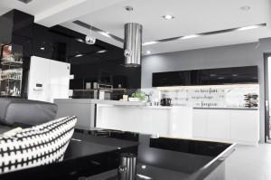 Kolorystka kuchni ograniczona została do czerni , bieli oraz szarości . Zabudowa w większości wykonana została na wysoki połysk. W czarnej zabudowie całej ściany kuchni oprócz niezliczonej ilości szafek kryją się drzwi do spiżarni. Dolne białe szafki kuchenne zaprojektowane i wykonane zostały w białym kolorze aby dodać kuchni lekkości. W wyspie kuchennej znajduje się płyta indukcyjna, nad którą znajduje się okap w formie stalowej rury , który sam w sobie stanowi element dekoracyjny przez co nadaje wnętrzu charakteru industrialnego.Oświetlenie sufitowe ukryte w niszach  jeszcze mocniej podkreśla prostotę projektu. Zabawnym akcentem jest fototapeta z napisami umieszczona pod szklaną taflą pomiędzy szafkami kuchennymi.