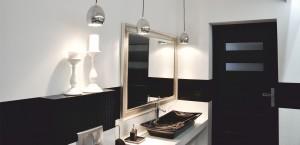 Aby przełamać surowość tej łazienki powieszone zostało lustro w srebrnej, stylizowanej ramie. Dość nietypowym rozwiązaniem było zastosowanie czarnej umywalki, która dodatkowo została podkreślona prze biały blat , na którym stoi.