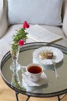 Salon w romantycznym domu wśród jabłoni, utrzymany w bieli i beżach. Wnętrze eleganckie, ale przytulne, pełne detali i ciekawych drobiazgów, które budują sielankowy klimat.