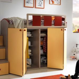 Dzięki umieszczeniu łóżka na szafie zyskujemy w pokoju wolną przestrzeń. Fot. Giessegi.