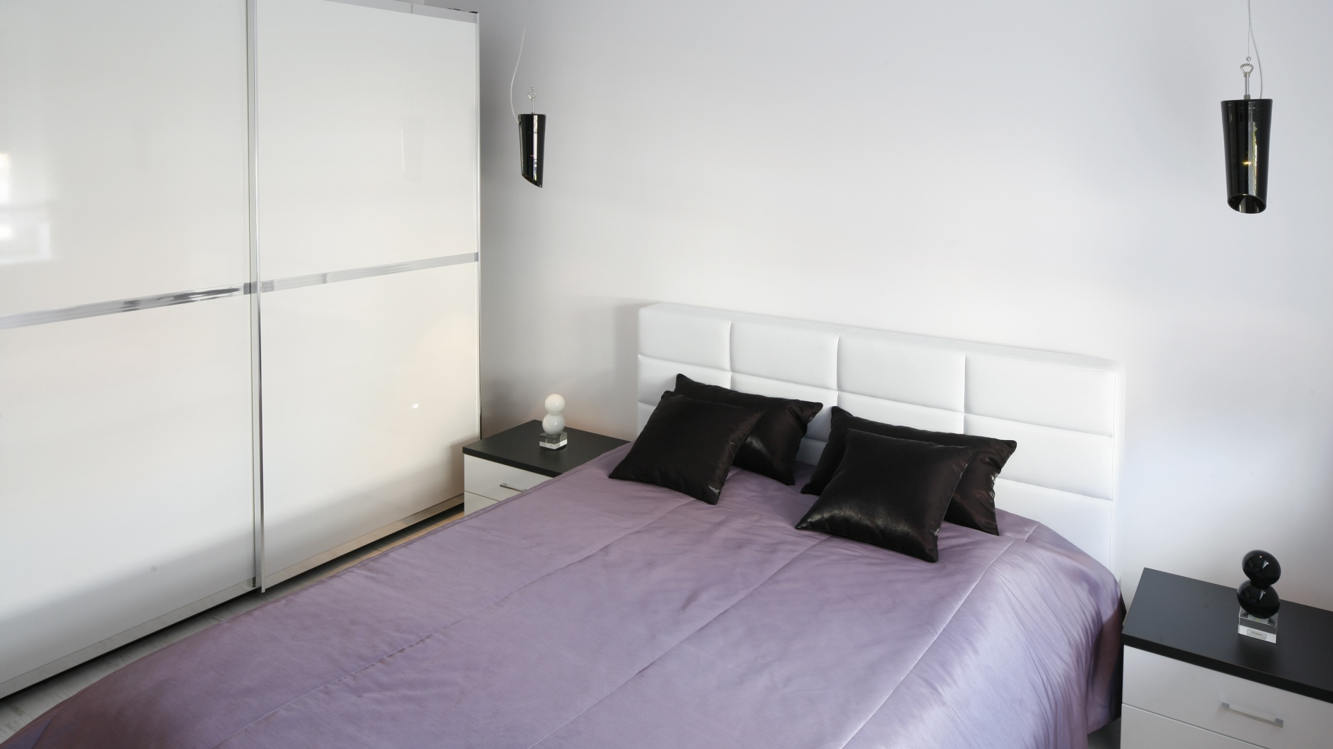 Wszechobecna biel zdominowała sypialnię. Nie znaczy to jednak, że nie znalazło się tu miejsce dla innych kolorów. Wręcz przeciwnie czerwień i subtelny odcień fioletu konsekwentnie przewijają się w każdym detalu. Projekt Joanna Ochota. Fot. Bartosz Jarosz.