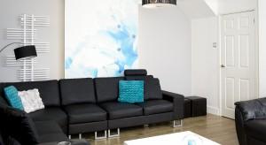 Nowoczesny pokój dzienny został skomponowany w kontrastowej bieli i czerni. Charakteru dodają mu turkusowe dodatki oraz piękny obraz na głównej ścianie. To wnętrze, w którym aż chce się wypoczywać!